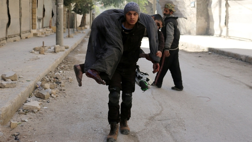 A Syrian civil defence volunteer carries an injured man following a reported air strike on Aleppo's rebel-held neighbourhood of Bab al-Nayrab
