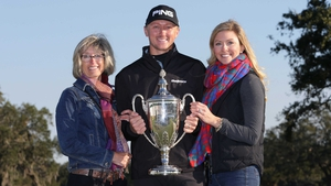 Mackenzie Hughes poses with the trophy alongside his wife and mother
