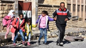 A Syrian man evacuates children from a school reportedly hit by rebel rocket fire in the Furqan neighbourhood of the government-held side of west Aleppo