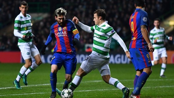 Lionel Messi of Barcelona (L) is tackled by Tomas Rogic of Celtic (C)