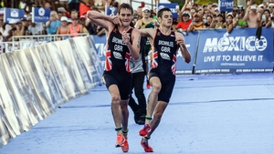 Alistair Brownlee (L) helps his brother Jonnny at the World Triathlon Championships 2016