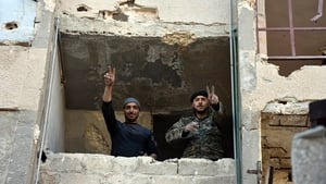 Syrian soldiers make a V for victory sign in Aleppo's eastern Masaken Hanano area