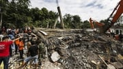Indonesian rescuers use an excavator to search for victims in Aceh