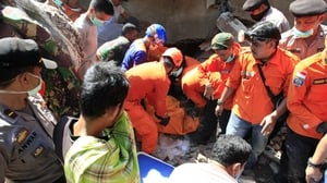 Indonesian rescue workers pull victims from destroyed buildings
