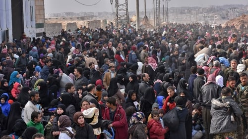 Syrian families, fleeing from various eastern districts of Aleppo, queue to get onto governmental buses