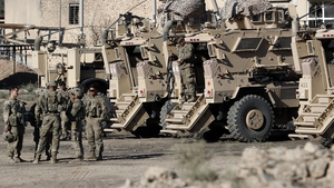 US soldiers are seen next to their armoured vehicles near an Iraqi army base on the outskirts of Mosul on 23 November