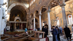 Security officials and people inspect the damage inside St Peter and St Paul Coptic Orthodox Church
