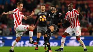 Dusan Tadic (C) of Southampton controls the ball under pressure of Glenn Whelan (L) and Bruno Martins Indi