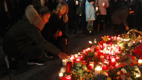 A woman leaves flowers and candles at the area where the attack took place