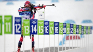 A biathlon competitor shoots at the targets on the range