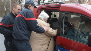 An elderly woman is helped by rescue workers