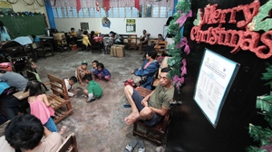 Filipino villagers with their belongings rest inside a school classroom turned into a temporary evacuation centre
