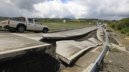 A truck drives by next to damage caused on a highway on Chiloe Island off the Pacific coast of southern Chile