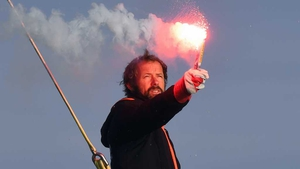French skipper Thomas Coville holds a burning flare onboard his 'Sodebo Ultim' multihull as he arrives in the port of Brest