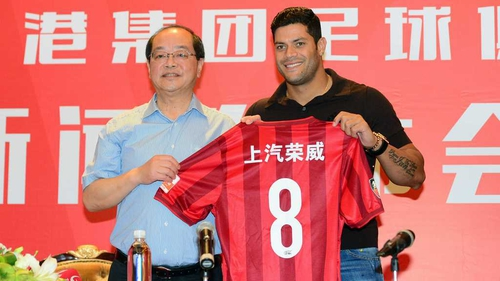 Hulk (R) poses with his new jersey during a press conference after joining Shanghai SIPG