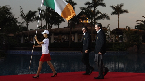 Rory McIlroy walks behind the Irish flag alongside team mate Graeme McDowell before the 2011 World Cup of Golf