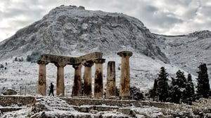 A person walks by the snow-covered temple of Apollo in Ancient Corinth, Greece