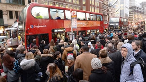 People queue for buses at Bishopsgate in the City of London