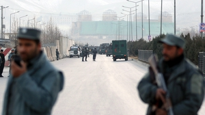 Afghan security officials block a road to parliament in Kabul after blasts