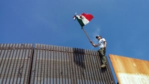 A US protester waves a Mexican flag at a border wall that divides Mexico and the US in Tijuana