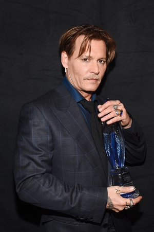 Johnny Depp also looks a little stunned pictured with his award for Favourite Movie Icon