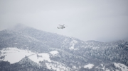 An Italian rescue helicopter flies towards the site of the hotel