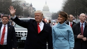 US President Donald Trump waves as he walks with US First Lady Melania Trump during the inauguration parade in Washington