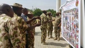 Soldiers take pictures of a banner showing the most wanted Boko Haram members in Maiduguri