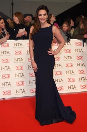 Danielle Lloyd chose an elegant figure hugging navy backless dress, with a slight train
