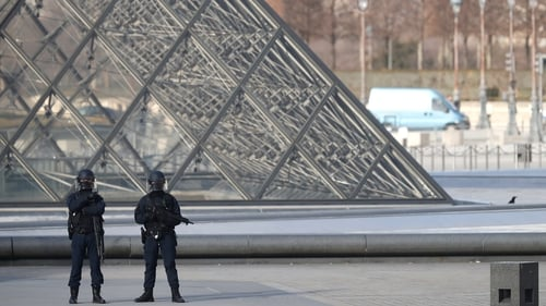 Police officers stand guard near the Pyramid of Le Louvre Museum, close to the Carrousel du Louvre