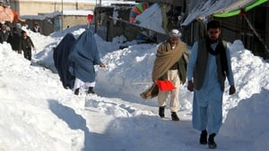 People make their way through a snowy road in Ghazni, Afghanistan today