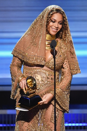 Beyoncé and her bump accepting the Best Urban Contemporary Album award for 'Lemonade'. We've never seen sheer, nude and embellished maternity wear before but we love it.