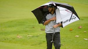 Dustin Johnson prepares to putt on the fourth hole in the rain in California