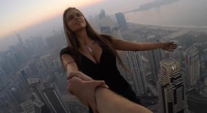 Russian model Viktoria Odintcova dangling over the edge of one of the world's tallest skyscrapers