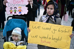 A child refugee carries a sign during a demonstration in Athens 21 January, 2017