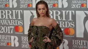 Rita Ora is not nominated for any Brit Awards this year but donned an opulent glittering green gown with a corset-style top half leading into a sheer full skirt for the occasion