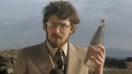 RTÉ reporter Jim Fahy holding a bottle of poteen (1977)