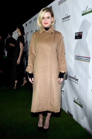Alice Eve keeps it simple and glam with a red lip and camel coat.