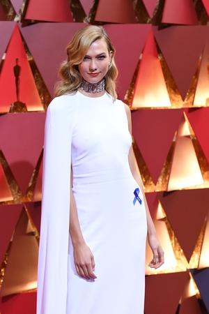 Model Karlie Kloss looks divine in Karlie Kloss in Stella McCartney, Nirav Modi jewelry plus that ACLU blue ribbon.