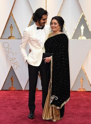 Dev Patel and his mother Anita! Dev looks so handsome in custom white Burberry.