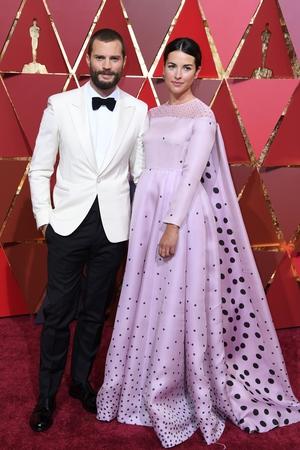 Jamie Dornan and his wife British actress Amelia Warner wore a baby pink, floor-skimming gown