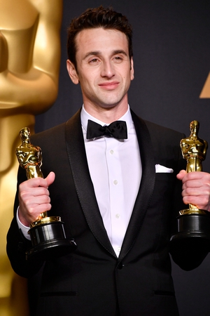 Composer Justin Hurwitz holds his two Oscars for the music behind La La Land