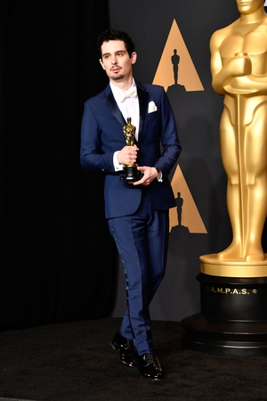La La Land's Damien Chazelle poses in the press room with the Oscar for Best Director
