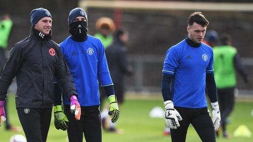 Kieran O'Hara (right) on the Manchester United training ground alongside the masked David De Gea