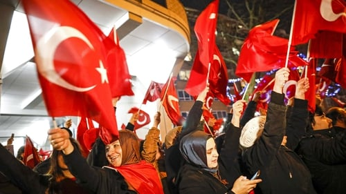 People wave Turkish flags as they protest outside the Turkish consulate in Rotterdam