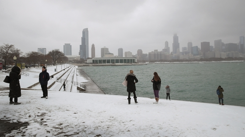 People walk along a snow-covered lakefront near downtown Chicago
