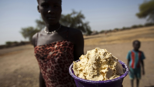 A woman holds out a bowl of partially boiled maize in South Sudan's Unity State