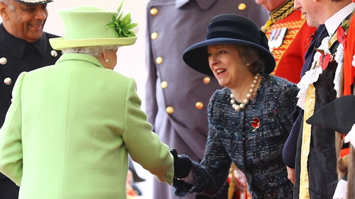 Queen Elizabeth shakes hands with Theresa May at an event last year