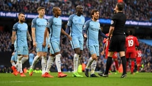 Manchester City players approach referee Michael Oliver during their game with Liverpool