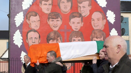 The coffin of Martin McGuinness is carried in procession past a mural in the Bogside